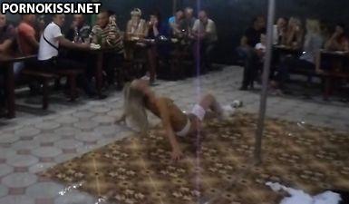 Длинноногая блондиночка в белых чулках сексуально вертится вокруг шеста в ресторане